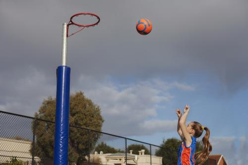 A girl playing Saturday morning netball throwing the ball