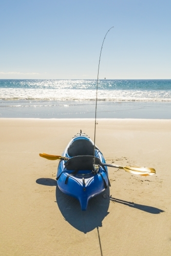 A kayak sitting on a beach with a paddle and fishing rod on board