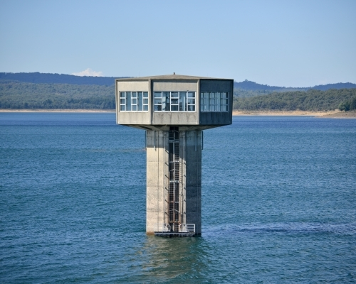 A large control tower in a freshwater reservoir