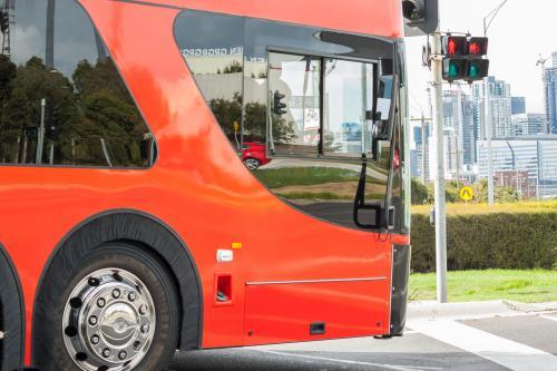 A large red bus waits at traffic lights
