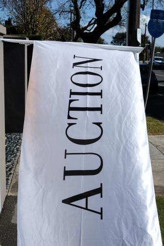 A large white flag advertising a property auction
