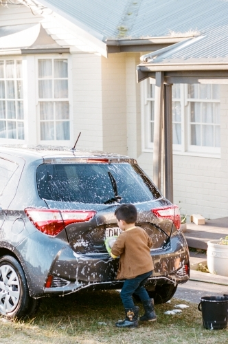 A Little Boy Washing Car in the Front Porch