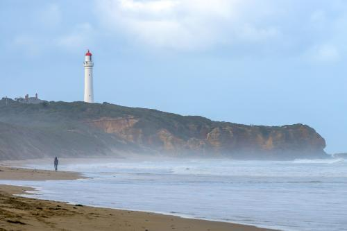 A lone figure on a beach below cliffs and a lighthouse