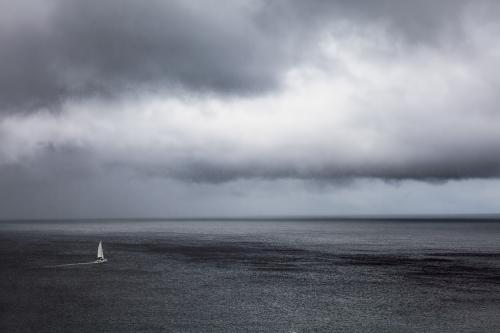 A lone yacht sailing the ocean under stormy grey skies