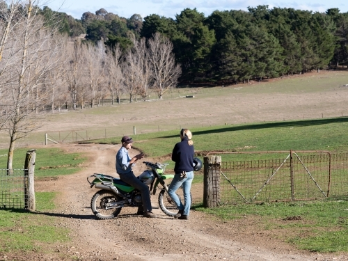 A male farmer on a motorbike in discussion with a female farmhand