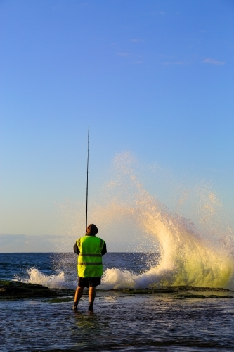 A man in his forties rock fishing at Wombarra Headland on the Illawarra Coast, NSW