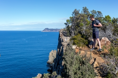 A man standing on the cliff by Tasmania's Cape Hauy on the Three Capes Track in the Tasman Peninsula