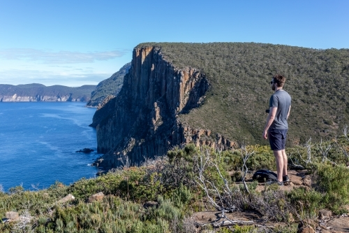 A man stands looking over Tasmania's Cape Hauy on the Three Capes Track in the Tasman Peninsula