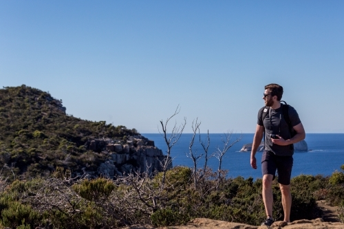 A man walking up the track to Tasmania's Cape Hauy on the Three Capes Track in the Tasman Peninsula