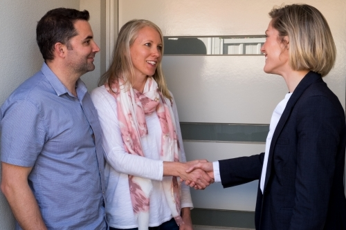 A mature couple look pleased shaking hands at the front door with a well presented business woman.
