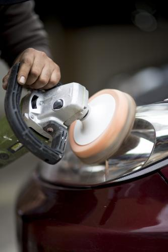 A mechanic buffers the headlight of a vehicle during a routine service.
