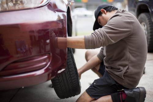 A mechanic inspects a tyre during a vehicle service.