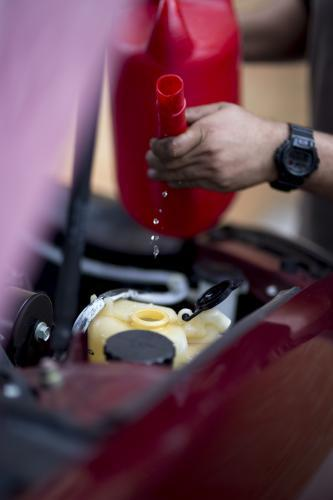 A mechanic refills windscreen washer fluid.