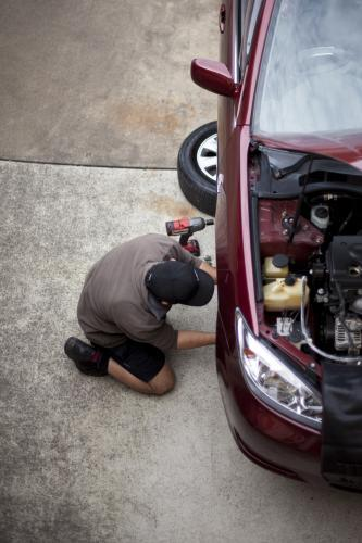 A mechanic services a vehicle.