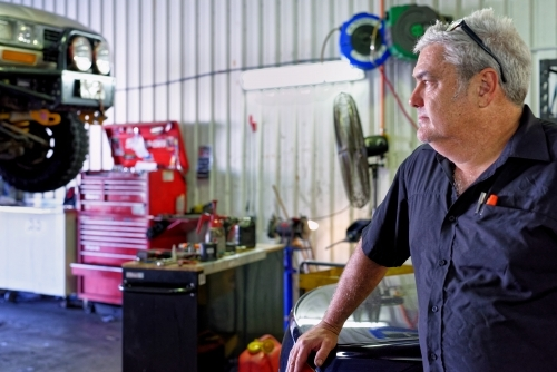 A mechanic standing in his workshop on the Gold Coast looking out