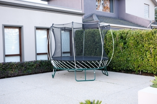 A new trampoline sits in the driveway of a modern home