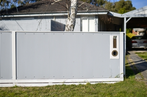 A new white corrugated fence in front of a single storey house