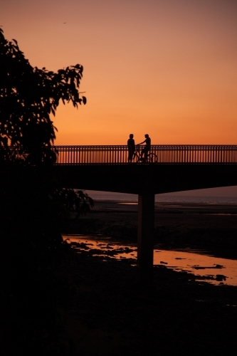 A pedestrian and cyclist on a bridge at sunset