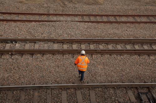 A person walking over three train tracks from overhead