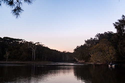 A quiet lake at dusk surround by bush and tree with small boats docked on the right.
