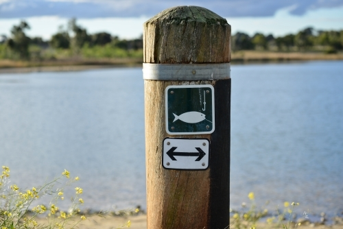 A sign post advising people that fishing is allowed on this side of the lake