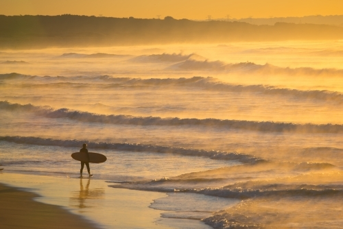 A single surfer heads into the waves at dawn