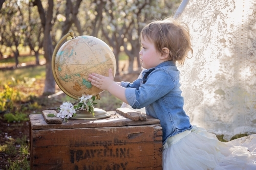 A Small Girl Holding a World Globe in a Flower Orchard