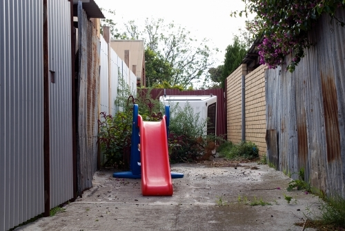 A small red childrens slide in an alleyway