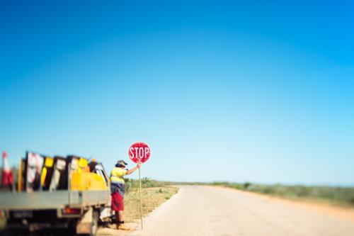 A solitary road worker holds a stop sign on a deserted road in the middle of nowhere