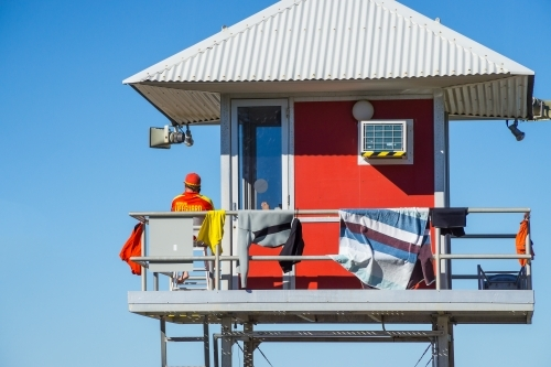 A surf lifeguard sitting in a watch tower with a corrugated tin roof.
