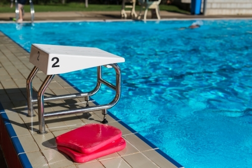 A swimming block with the number 2 and red kickboards at a swimming pool