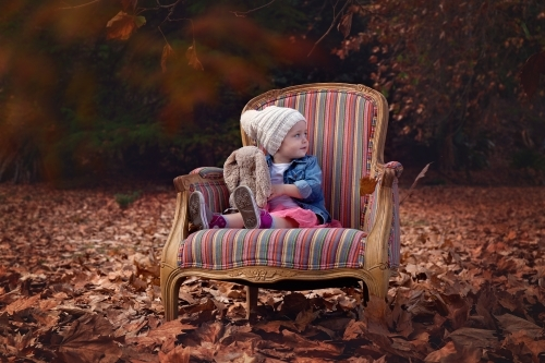A Toddler Girl Sitting on a Chair amongst Autumn Leaves