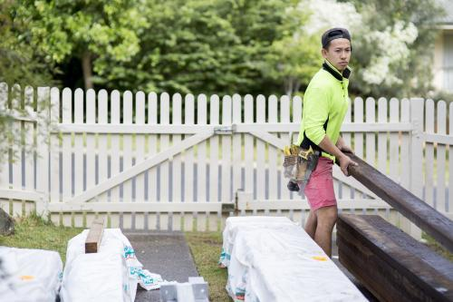 A tradesman carries a wooden beam on a home renovation site.