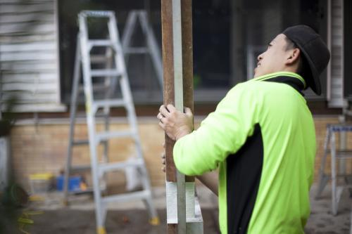 A tradesman checking the vertical axis of a wooden post.