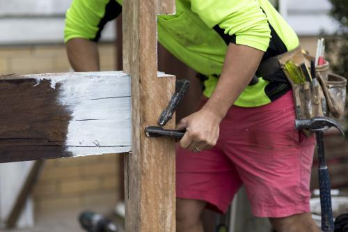 A tradesman fixing a wooden beam to a post.