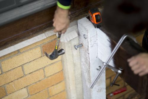 A tradesman hits a bolt into a wooden beam.