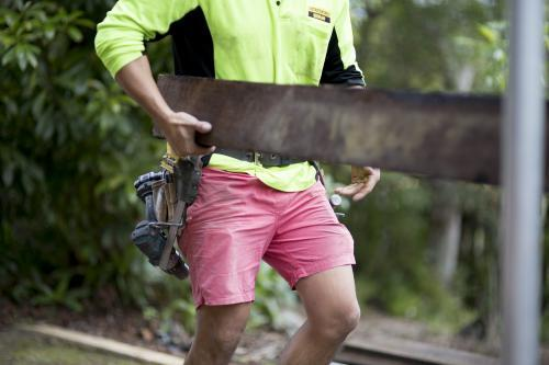 A tradesman lifts a wooden beam.