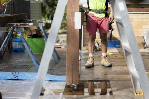 A tradesman standing outside on a home renovation site.