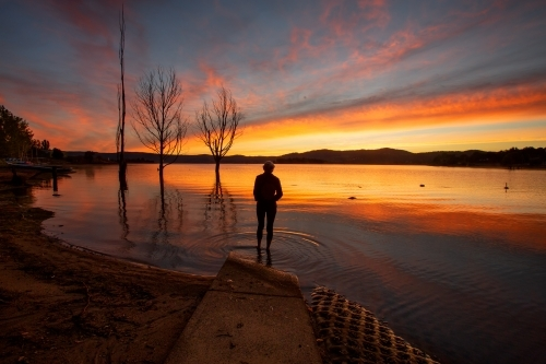 A traveller watching the beautiful colourful sky and reflections on Lake Jindabyne