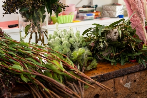 A variety of native and exotic flowers and greenery on a workbench