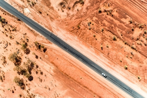 A white ute driving a rural highway straddled by red earth.