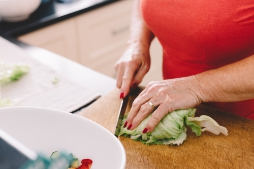 A woman chopping lettuce with a knife in a kitchen