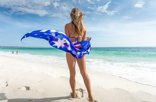 A woman stands on the beach with Australian flag sarong flapping in the wind