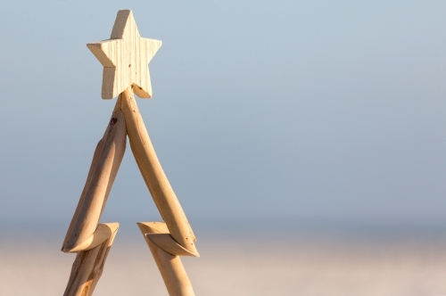 A wooden Christmas tree against a beach background with copy space.