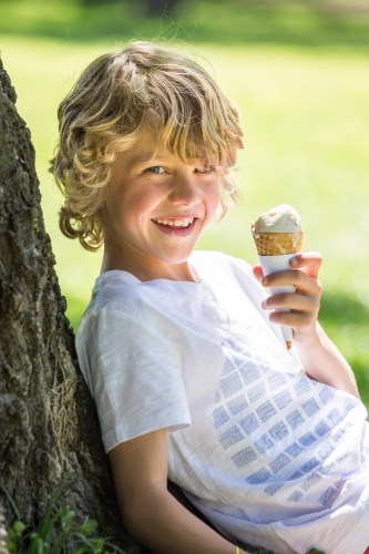 A young boy sitting against a tree eating an ice cream cone