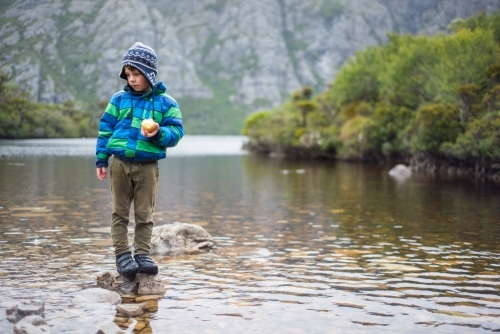 A young boy standing on a rock in a river