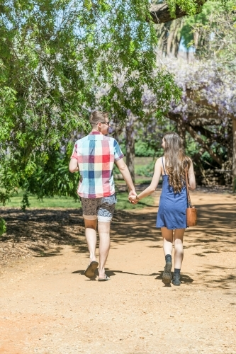 A young couple walking hand in hand down a garden path