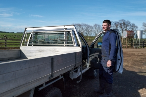 A young farmer standing next to his Ute
