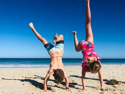 A young girl and boy doing handstands in swimming outfits on shoreline of beach on still summers day
