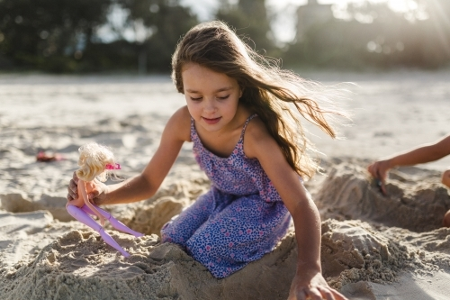 A young girl at the beach playing in the sand